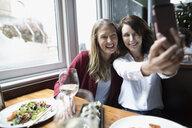Women friends taking selfie with camera phone at restaurant - HEROF15424