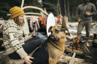 Woman with dog enjoying weekend surfing getaway, relaxing by campfire - HEROF15505