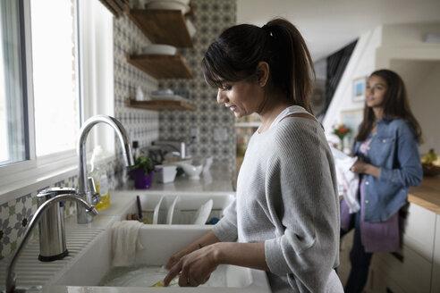 Woman washing dishes at kitchen sink - HEROF15526