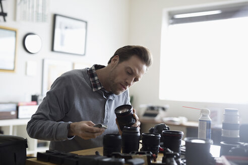 Focused male photographer cleaning camera lenses - HEROF15544