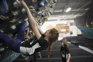Girl rock climber climbing wall at climbing gym - HEROF15619