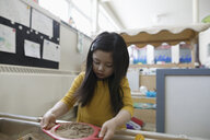 Focused preschool girl playing with sand in classroom - HEROF15637