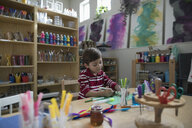 Focused preschool boy drawing with markers, making art and craft project in classroom - HEROF15643