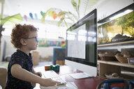 Focused preschool boy drawing at computer in classroom - HEROF15649