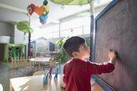 Focused preschool boy student at blackboard in classroom - HEROF15652