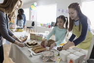 Girls in aprons selling desserts at bake sale in community center - HEROF15664