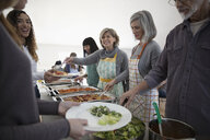 Happy senior women serving food at soup kitchen community dinner - HEROF15667