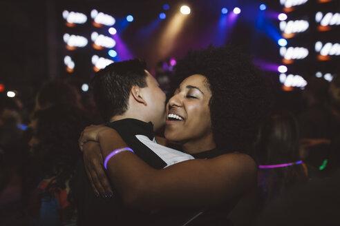 Happy young millennial couple hugging, dancing in nightclub - HEROF15670