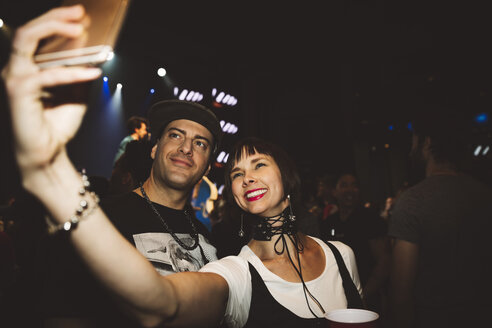 Happy couple taking selfie with camera at nightclub - HEROF15676