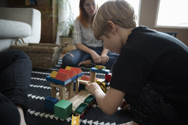 Focused boy playing with building block toys - HEROF15694