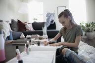 Girl painting fingernails with fingernail polish in living room - HEROF15703