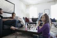 Girl painting fingernails with fingernail polish in living room - HEROF15706