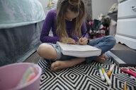 Focused girl drawing on floor - HEROF15709