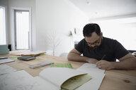 Focused male artist sketching, drawing on paper at table - HEROF15712