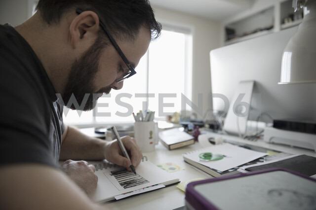 Focused male illustrator sketching in home office - HEROF15715 - Hero Images/Westend61