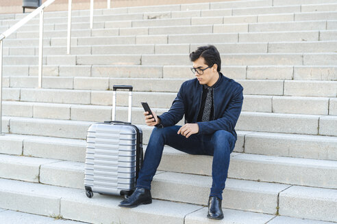 Fashionable young businessman with rolling suitcase sitting on stairs looking at mobile phone - AFVF02322