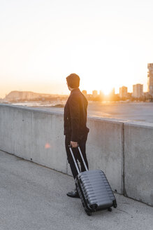 Spain, Barcelona, back view of young businessman with rolling suitcase watching sunset - AFVF02337