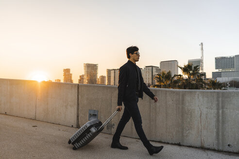 Spain, Barcelona, young businessman with rolling suitcase at sunset - AFVF02343