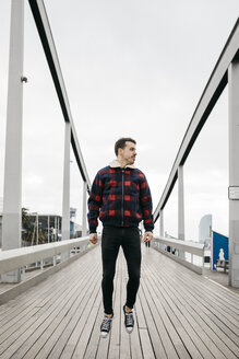 Young man wearing casual clothes jumping on a harbor bridge - JRFF02551