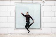 Young man with casual clothes jumping with a white wall and a large window in the background - JRFF02560