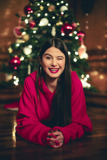 Portrait of winking teenage girl lying on the floor in front of Christmas tree - ACPF00414