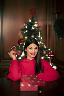 Portrait of smiling teenage girl with Christmas present - ACPF00420