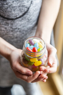 Glass of colourful sweet jellybeans on white wood, hands holding glass - SARF04082