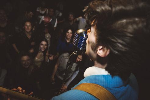 Musician singing at microphone at music concert - HEROF15787