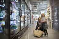 Mother and daughter with smart phone grocery shopping in refrigerated market aisle - HEROF15808