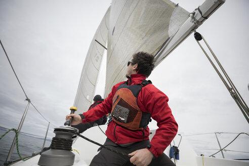 Man adjusting sail rigging on sailboat - HEROF15868