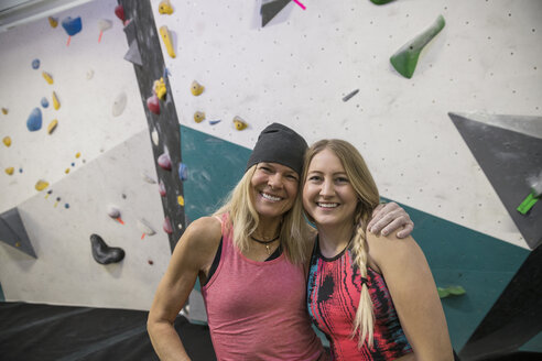 Portrait smiling, confident female rock climber friends hugging at climbing wall in climbing gym - HEROF15946
