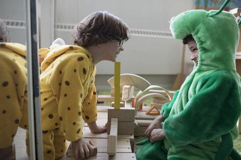 Preschool boys in costumes playing with wood blocks - HEROF15997