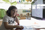 Portrait smiling, confident preschool girl student with headphones drawing at computer in classroom - HEROF16033