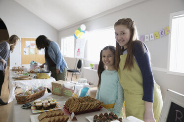 Portrait smiling girls in aprons selling desserts at bake sale in community center - HEROF16042