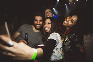 Playful, happy millennial friends taking selfie with camera phone, partying in nightclub - HEROF16054
