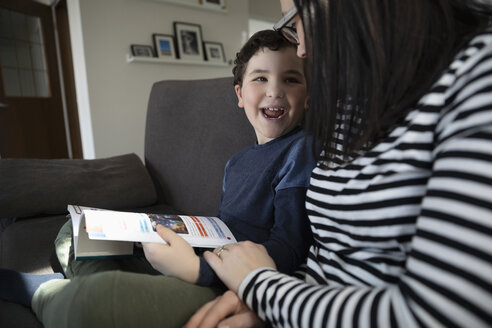 Playful, affectionate son reading book with mother on sofa - HEROF16090