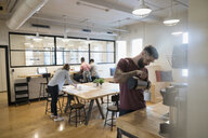 Architect pouring coffee at coffee pot in open plan office - HEROF16135