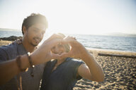 Affectionate couple forming heart-shape with hands on sunny ocean beach - HEROF16213