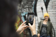 Young woman with camera phone photographing friend along graffiti wall - HEROF16243