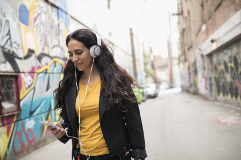 Young woman with headphones listening to music with smart phone in urban graffiti alley - HEROF16249