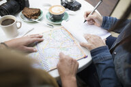 Women friends planning with map, drinking coffee at sidewalk cafe - HEROF16252