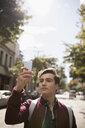 Young man using camera phone on urban street - HEROF16273