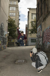 Young woman with camera phone photographing young man jumping on urban alley street - HEROF16276