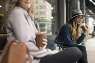 Young women friends drinking iced coffee on bench at sidewalk cafe - HEROF16288