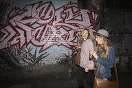 Young women friends drinking iced coffee, walking along urban graffiti wall - HEROF16291