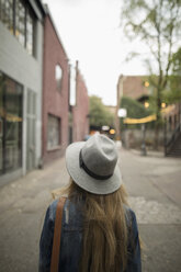 Young woman in fedora looking up on urban street - HEROF16294