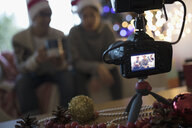 View through camera viewfinder of couple wearing Santa hats in Christmas living room - HEROF16330