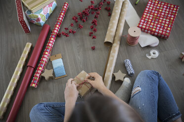 Teenage girl wrapping Christmas gifts on floor - HEROF16333
