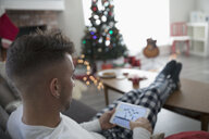 Young man in pajamas using digital tablet in Christmas living room - HEROF16336