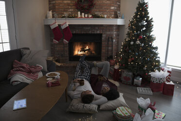 Young couple in pajamas laying, relaxing by fire near Christmas tree in living room - HEROF16342